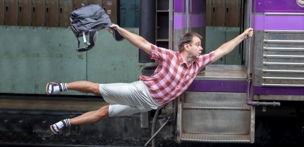 急いで電車に掴まる男性