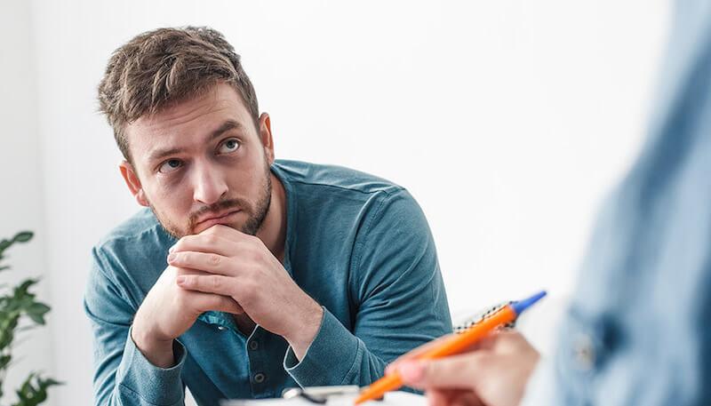 語学学校で先生の話を聞く不安な男性