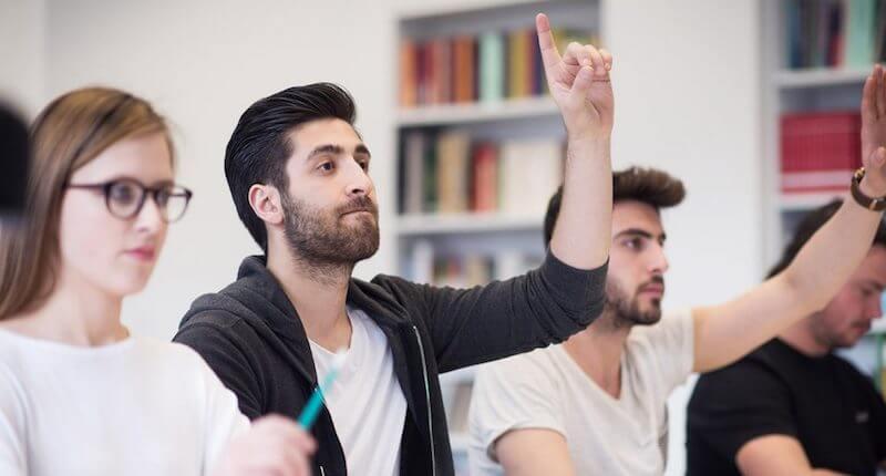 語学学校で手をあげる男性