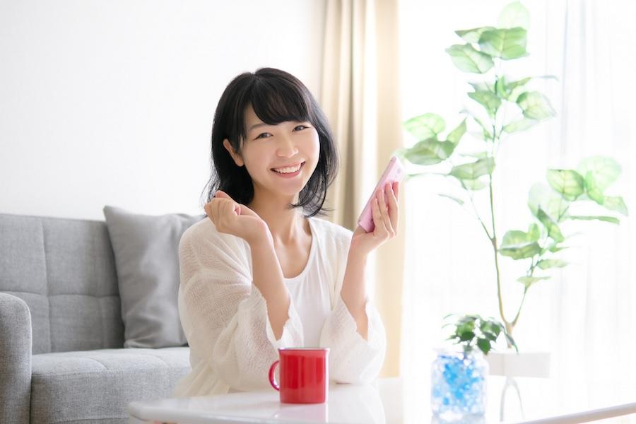 スマートフォンを持って微笑む女性